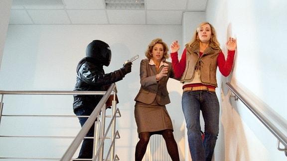 Mit der Waffe in der Hand dirigiert der Täter Rita Dreher (Carin Tietze, links) und Nathalie Schrade (Judith Richter, rechts) hektisch zum Hinterausgang.