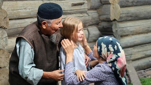 Kunbike (Ilgisa Gilmanowa, rechts) beruhigt Oksana (Marta Timofejewa, Mitte). Onkel Mansur (Rauis Sagitow) hatte das Mädchen vorm Ersticken gerettet.