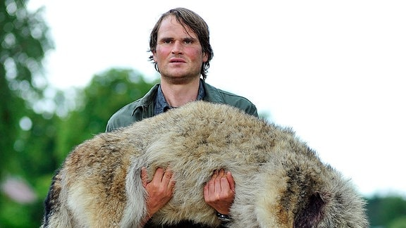 Waldner (Fabian Hinrichs) trägt den toten Wolf durch Kaskow.