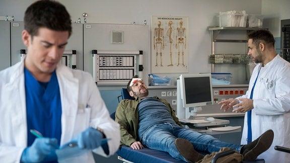 Nach einem Treppensturz kommt Axel Becker (Jens Kipper, M.) in die Notaufnahme. Matteo (Mike Adler, r.) und Ben (Philipp Danne, l.) hatten den Patienten für eine Nierentransplantation vorgesehen.