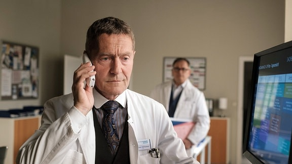 Hans-Peter Brenner (Michael Trischan, hinten) wundert sich, als er Dr. Kaminski (Udo Schenk, vorn) im Ärztezimmer aufgebracht russisch reden hört.