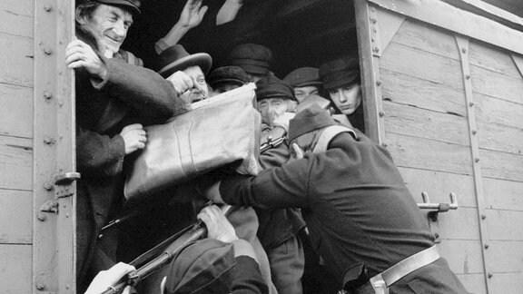 Deutsche Soldaten deportieren Juden, die in der Gaskammer eines Konzentrationslagers den Tod finden werden.
