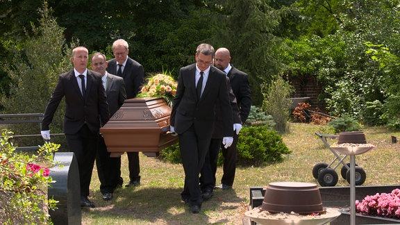 Fünf Personen tragen einen Sarg auf einem Friedhof.
