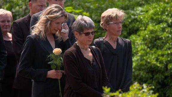 Trauernde Gäste einer Beerdigung auf dem Friedhof.