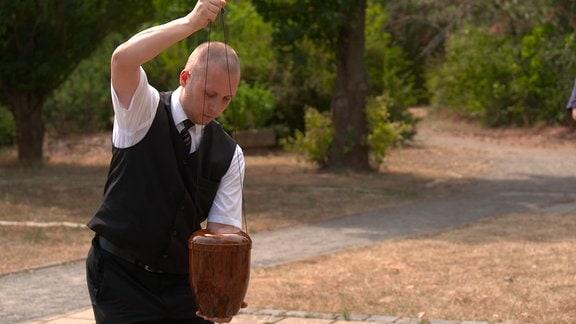 Ein Mann verstreut die Asche eines Verstorbenen aus einer Urne.