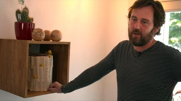 Bestatter Eric Wrede neben einer individuell gestalteten Urne.