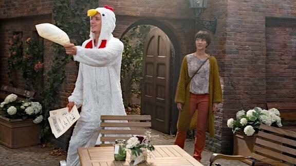 Anton (Jean-Luc Caputo, l. mit Anja Franke, r.) versucht mit Flugblättern und Straßenmusik, Hühnerpaten zu gewinnen.