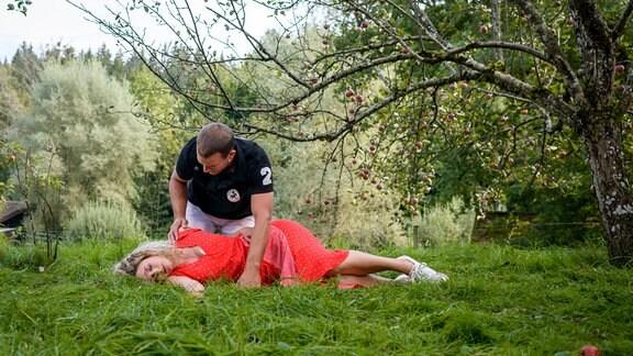 Tim (Florian Frowein, hinten) kümmert sich besorgt um die verletzte Franzi (Léa Wegmann, vorne).
