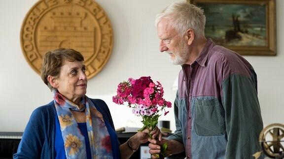 Katrin (Katharina Thalbach) reagiert mit verwundertem Blick auf den Blumenstrauß, den ihr Johannes (Ernst Stötzner) mitgebracht hat.