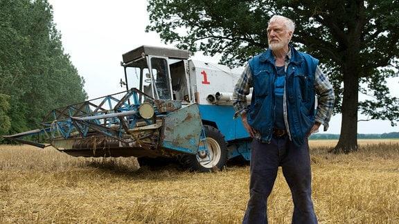 Johannes (Ernst Stötzner) steht breitbeinig, mit Händen in den Hosentaschen und ernstem Blick auf einem Feld.