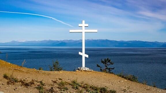 Blick von einer Anhöhe auf den Baikalsee. Am Rand der Klippe ist ein russisch-orthodoxes Kreuz errichtet.