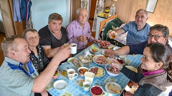 Mehrere Menschen sitzen an einem gedeckten Tisch und prosten sich zu.