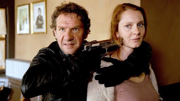 Der Gangster Daniele (Johannes Zeiler) möchte sich mit Petra (Daniela Schulz) als Geisel freipressen.