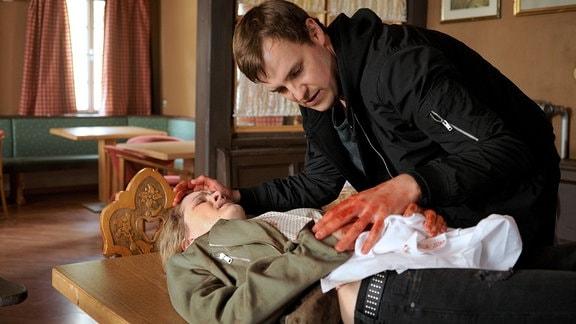 Stefan (Frederic Linkemann) ist über die schwerverletzte Francesca (Juliane Fisch) gebeugt.