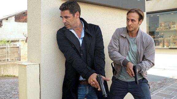Matteo (Tobias Oertel, li.) und Jonas Kerschbaumer (Gabriel Raab) stehen mit Pistolen in den Händen im Schutz einer Mauer.