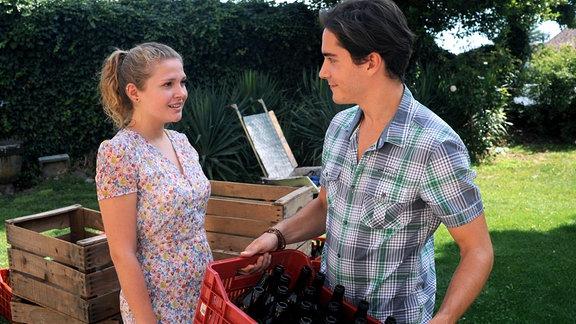 Laura (Charleen Deetz) steht neben (François Goeske), der eine Kiste mit Flaschen in der Hand hält.