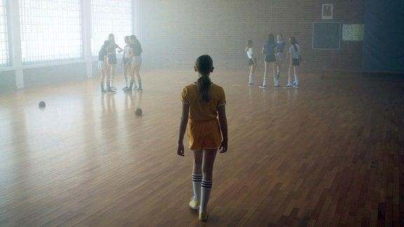 Ella (Ella Runge) als Kind in einer Sporthalle. Absets von ihr zwei Gruppen mit anderen Kindern.