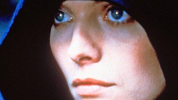 Isabeau d'Anjou (Michelle Pfeiffer) in menschlicher Gestalt, eine Kapuze tief ins Gesicht gezogen.