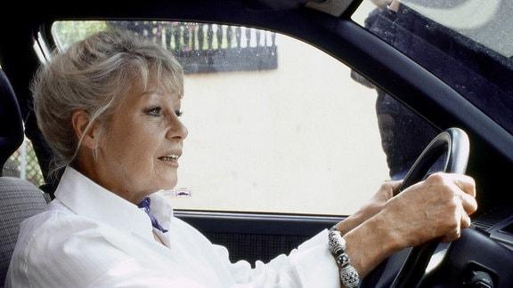 Edith Reger (Marita Böhme) am Steuer eines Personenkraftwagens.