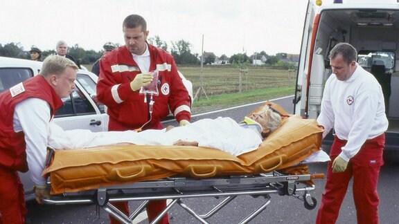 Schwer verletzt wird Edith Reger (Marita Böhme) nach einem Verkehrsunfall ins Krankenhaus gebracht.