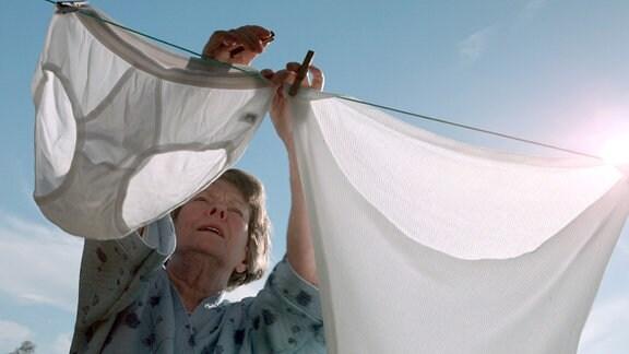 Elisabeth (Monika Lennartz) hängt Wäsche auf eine Leine.