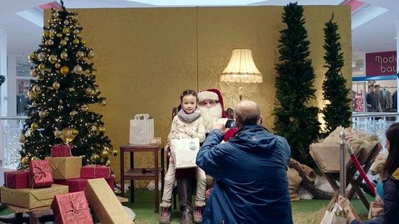 Klaus (Matthias Brenner) lässt sich als Weihnachtsmann verkleidet mit einem kleinen Mädchen fotografieren.