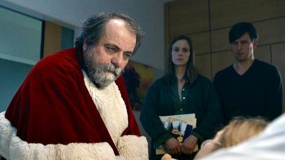 (Matthias Brenner) als Weihnachtsmann verkleidet. In einem Krankenbett liegt die kleine Clara (Helene Pieske, liegend), hinter ihr stehen ihre Eltern (Julia Jäger, Peter Schneider).