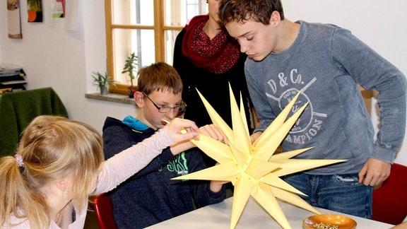 Die Brüder-Unität unterhält Krankenhäuser, Heime und Schulen. Hier bauen Schüler aus der Oberstufe der Herrnhuter Förderschule einen Stern. Erstmal nachmachen!