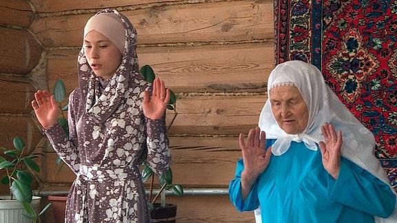 Kamilla (l) betet mit Ihrer Oma auf dem Dorf.