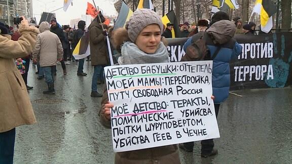 """Kamilla trägt das Textplakat auf einer Protestdemonstration mit folgendem Inhalt: """"Die Kindheit meiner Oma: Tauwetter. Die Kindheit meiner Mama: Perestrojka, freies Russland. Meine Kindheit: Terrorakte, politische Morde."""""""