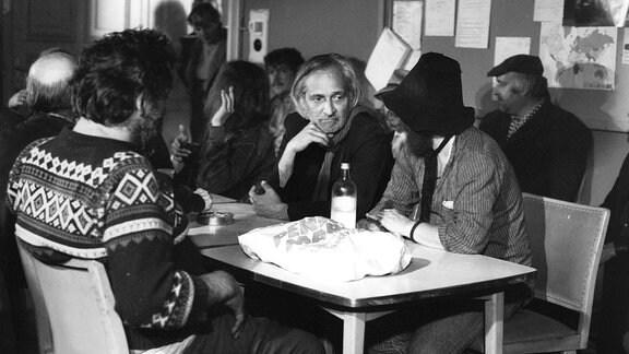 Bildmitte: Paul Albert Krumm. Eine Personengruppe sitzt an einem Tisch.