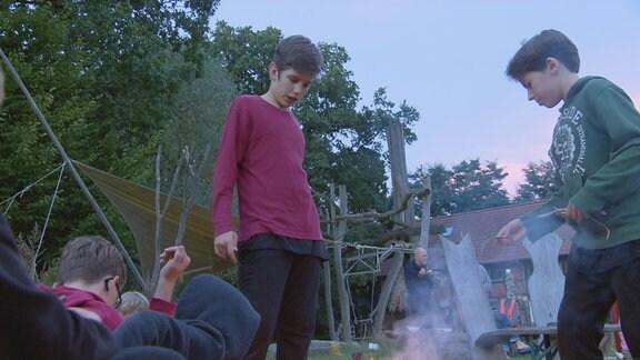 Zum freien Leben im Ökodorf gehört für Felix und Jona (re.) auch Lagerfeuerromantik.