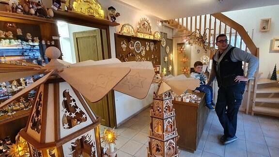 Ein Mann und ein Kind in einem Wohnhaus, das mit etlichen leuchtenden Weihnachtsholzfiguren dekoriert ist.