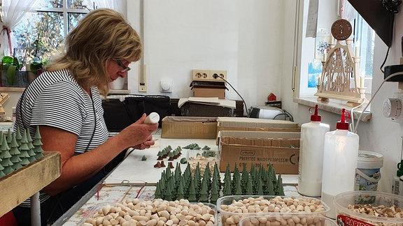 Eine Frau arbeitet in einer Werkstatt an hölzernen Tannbaum-Figuren.