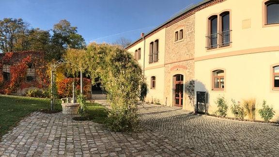 Der Vorplatz eines sanierten Ritterguts mit einem Brunnen.