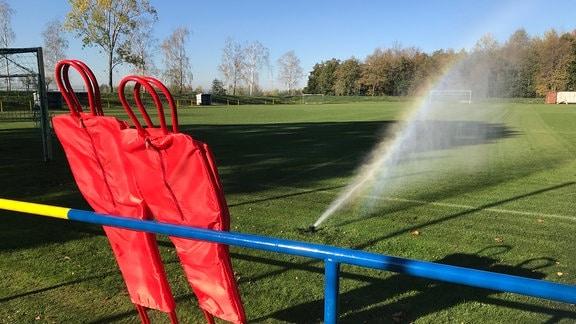Ein Fußballplatz, der mit einem Rasensprenger gewässert wird.