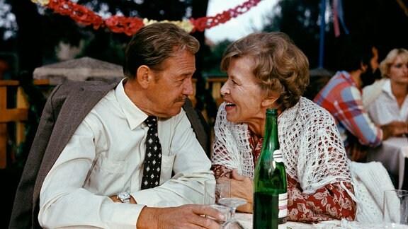 """Spartenvorsitzender Timm (Herbert Köfer) und seine Ehefrau Elfriede (Helga Göring) in der Kleingartenanlage """"Ulenhorst""""."""