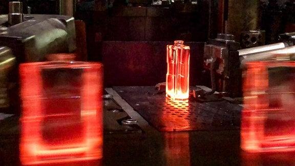 Auf der Glasmaschine entstehen aus flüssigem Glas die Flakons – bis zu 500 Stück pro Minute. Bei Temperaturen um 1000°C werden sie mittels Pressluft in Stahlformen ausgeblasen.
