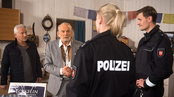 Hannes (Claus Dieter Clausnitzer, 2.v.l. mit Gerry Hungbauer, l.) fällt aus allen Wolken, als er wegen seines Koffers verhaftet wird (mit Komparsen, r.).