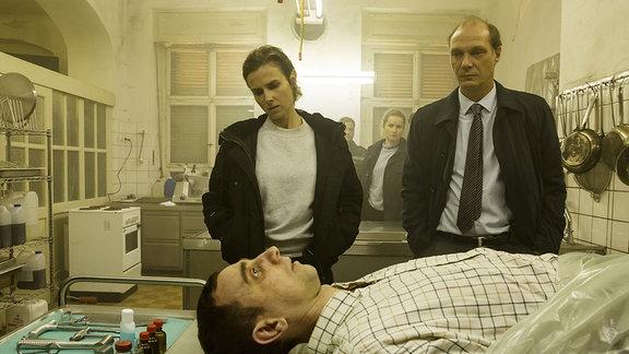 Karin Gorniak (Karin Hanczewski), Leonie Winkler (Cornelia Gröschel) und Peter Michael Schnabel (Martin Brambach) betrachten die Leiche in der Küche des verlassenen Hotels.