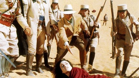 Der Archäologe Desmond Jordan (Michael York, knieend) und sein Gefährte Orso (Diego Abatantuono, 2.v.l.) retten das Leben der geheimnisvollen Anthea (Andie MacDowell, liegend).