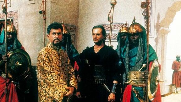 Der Kalif von Timbuktu (James Farentino, Mitte l.) glaubt, dass der Sprechende Berg einen Schatz verbirgt. Diesen will er mit Hilfe des Wüstenbanditen El Halem (Miguel Bosé, Mitte r.) erbeuten.