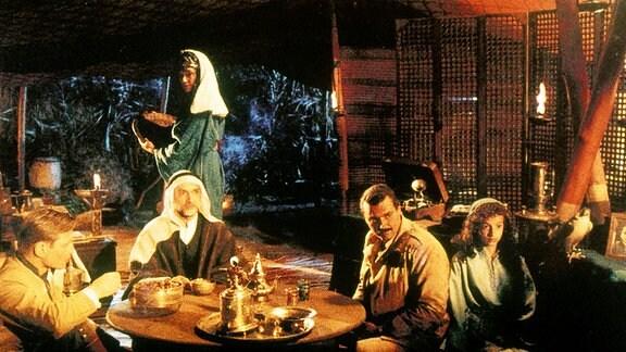 Desmond Jordan (Michael York, l.) und sein Weggefährte Orso (Diego Abatantuono, 2.v.r.) finden Zuflucht in der Oase des Juden Sholomon (Ben Kingsley, 2.v.l.), der dort mit seiner Frau Yasmine (Delia Boccardo, hinten) und deren Tochter Parizade (Radost Bokel) lebt.
