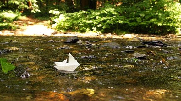 Papier-Boot im Wasser, eine Metapher für den Fluss des Lebens