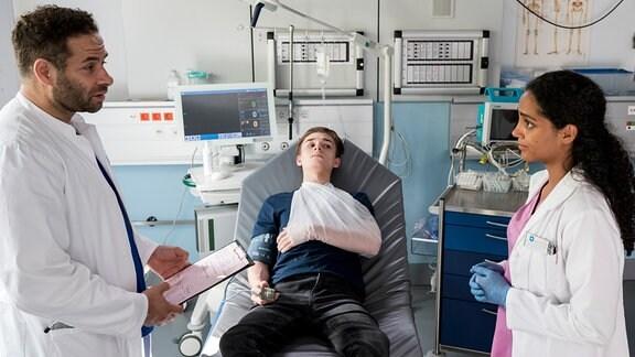Matteo Moreau (Mike Adler, l.) und Emma Jahn (Elisa Agbaglah, r.) diagnostizieren bei Nick Kranz (Niklas Post, M.) eine ausgekugelte Schulter.