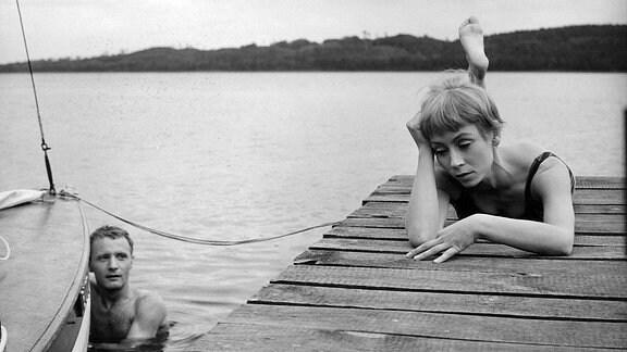 Jürgen Hentsch (Kaspar) im Wasser; auf Bootssteg liegt Jutta Hoffmann (Karla) mit Kopf auf Hand gestützt; er schaut sie an; Mimik Hoffmann ernst, traurig, nachdenklich