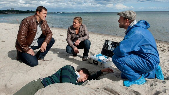 Am Strand von Travemünde wurde die Leiche von Björn Aufderheide gefunden. Von links nach rechts: Finn Kiesewetter (Sven Martinek), Sandra Schwartenbeck (Marie-Luise Schramm) und Pathologe Dr. Strahl (Christoph Tomanek), Björn Aufderheide (Leiche: Komparse)