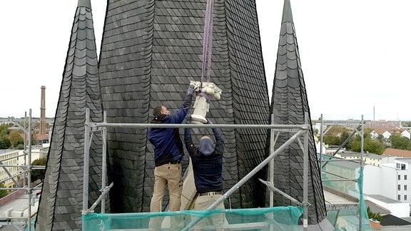 Die Kreuzblumen am Dach der St. Ambrosius-Kirche in Magdeburg waren alle zerstört oder verschwunden. Nun setzen die Steinmetze neue Zierelemente in luftiger Höhe.