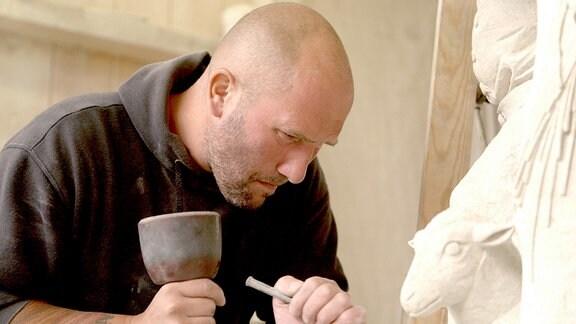 Steinmetz Rico arbeitet konzentriert an einer Skulptur der Jahreszeitenkinder.