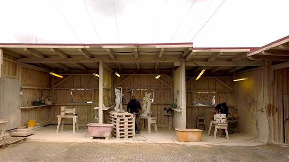 """Auf dem Betriebsgelände der Bauhütte arbeiten Rico und Dennis an ihren """"Jahrenzeiten-Kindern""""."""